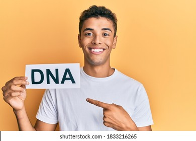 Young handsome african american man holding dna word smiling happy pointing with hand and finger