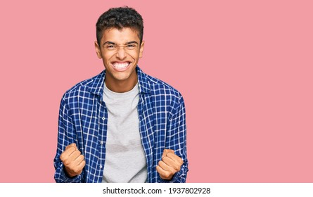 Young handsome african american man wearing casual clothes very happy and excited doing winner gesture with arms raised, smiling and screaming for success. celebration concept.