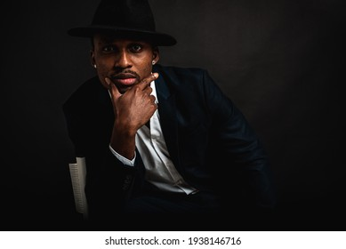 young, handsome african american man in stylish suit and glasses sitting on a chair on a dark background. Selective focus. Sign language, place for inscription