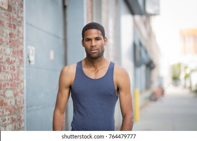 Young handsome African American man in tank top in the rough neighborhood