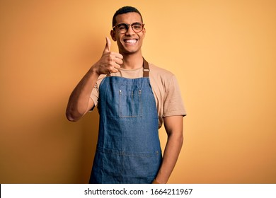 Young handsome african american shopkeeper man wearing apron over yellow background doing happy thumbs up gesture with hand. Approving expression looking at the camera showing success.