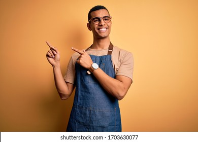 Young handsome african american shopkeeper man wearing apron over yellow background smiling and looking at the camera pointing with two hands and fingers to the side.