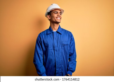 Young handsome african american worker man wearing blue uniform and security helmet looking away to side with smile on face, natural expression. Laughing confident.