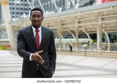 Young handsome African businessman greeting in front of modern building at Bangkok city