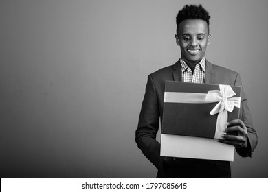 Young handsome African businessman holding gift box