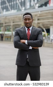 Young handsome African businessman standing in front of modern building at Bangkok city