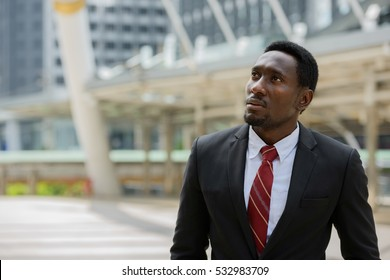Young handsome African businessman thinking in front of modern building at Bangkok city