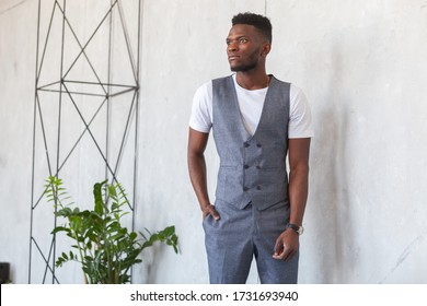 Young handsome african man in grey vest and trousers posing next to a metal structure in the loft style against a gray concrete wall