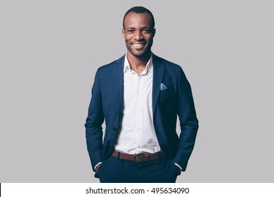 Young and handsome. Handsome young African man in smart casual jacket holding hands in pockets and smiling while standing against grey background