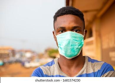 Der junge gut aussehende Afrikaner trug eine Gesichtsmaske, die ihn davor bewahrte, ihn vor dem Ausbruch in seiner Gesellschaft zu bewahren.