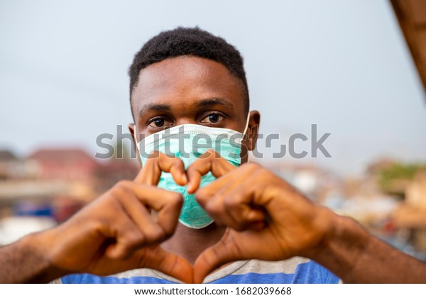 young handsome african nigerian man wore face mask preventing, prevent, prevented himself from the outbreak in his society and did a love sign.