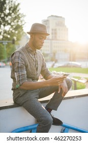 young handsome afro black man sitting outside in the city back light, using a smartphone handheld, looking downward and touching the screen - technology, social network, communication concept
