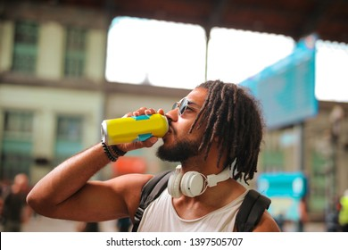 Young handsome Afro man having a drink on the street.