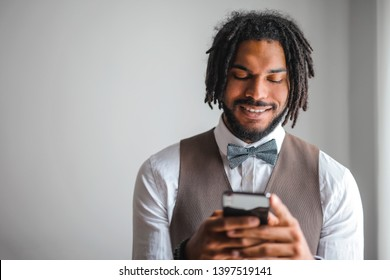 Young handsome Afro man texting on a smartphone.