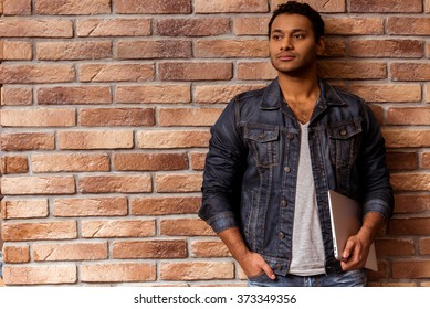 Young handsome Afro-American man in jeans jacket holding closed laptop and looking away while standing against brick wall