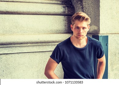Young handsome American Man with little beard, wearing black T shirt, sitting on street in New York, looking at you.