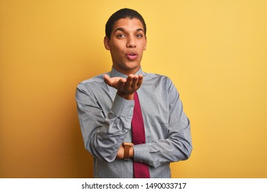 Young handsome arab businessman wearing shirt and tie over isolated yellow background looking at the camera blowing a kiss with hand on air being lovely and sexy. Love expression.