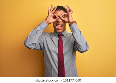 Young handsome arab businessman wearing shirt and tie over isolated yellow background doing ok gesture like binoculars sticking tongue out, eyes looking through fingers. Crazy expression.