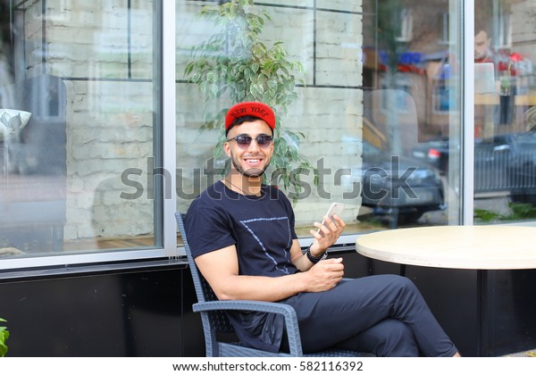 Young handsome arabic guy uses phone, sits chatting, smiles and looks in camera, sitting on wicker gray chair, bent leg at knee and throwing it on foot at table on background of panoramic windows and