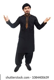 Young handsome Arabic Pakistani Indian Muslim boy man raising his hands with his eyes up and laughing while standing against white background and showing thumb on camera front in black kameez shalwar.