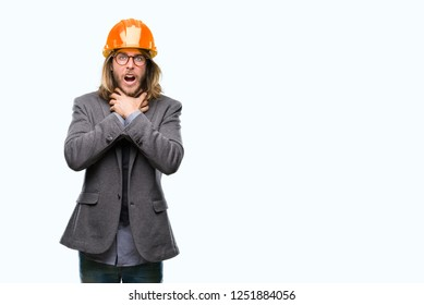 Young handsome architec man with long hair wearing safety helmet over isolated background shouting and suffocate because painful strangle. Health problem. Asphyxiate and suicide concept.