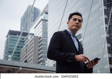 young handsome asian business man wearing modern black suit reading information about finance news with mobile smart phone in building city background, network technology, internet, successful concept