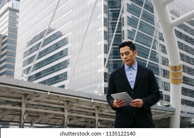 young handsome asian business man standing and working about finance on digital tablet in office building, technology, internet, investment, stock market and global business concept