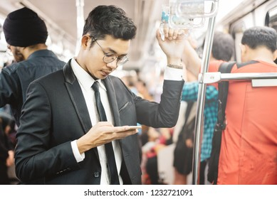 young and handsome asian businessman using smarphone in a commuter train. concept of business people and wireless technology