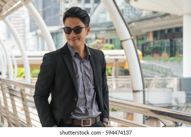 Young handsome Asian businessman wearing sunglasses standing in a modern city.