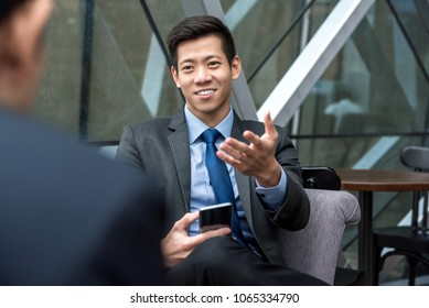 Young handsome Asian Chinese businessman sitting and  talking with his partner in cafe