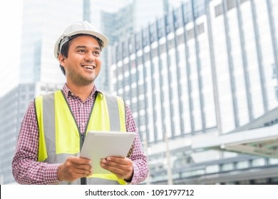 Young handsome asian civil engineer holding tablet looking forward and thinking, planning on construction building background. Evolution construction concept.