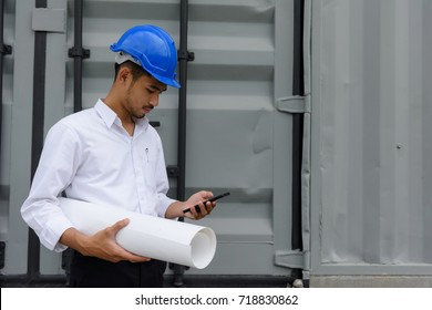 Young handsome Asian field engineer man, 20-30 years old, checking construction plan on smartphone and carrying paper plan near site building with copy space for text. Business engineering concept.