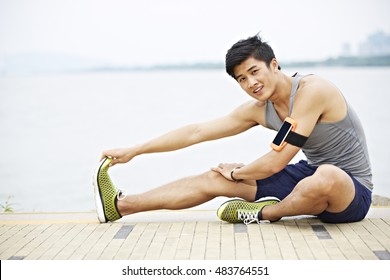 young handsome asian jogger wearing fitness tracker stretching a leg by lake looking at camera smiling