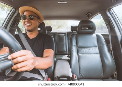 Young handsome asian man driving car to travel.