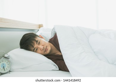 Young handsome Asian man lie on one's side and covered by blanket on the bed in the bedroom.
