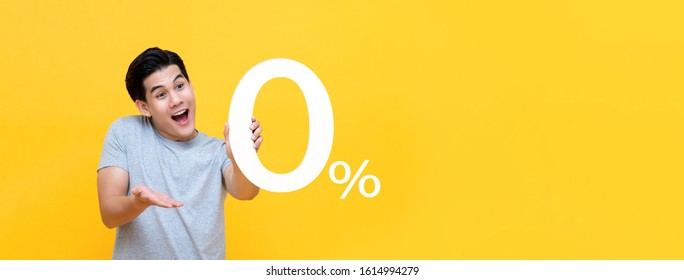 Young handsome Asian man offer 0% on yellow banner background with copy space for no interest installment payment concept