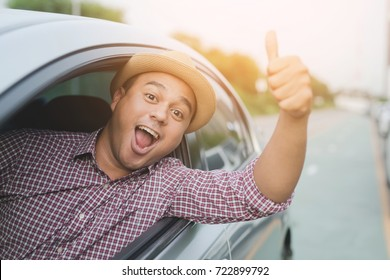 Young handsome asian man showing thumbs up in while driving car.