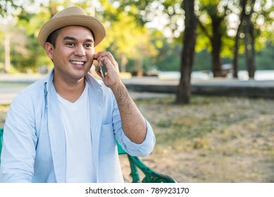Young handsome asian man talking on phone in the park