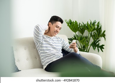 Young handsome asian man using modern mobile smart phone sitting on a couch at home