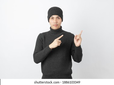 Young handsome asian man wearing grey sweater and beanie pointing to the side with fingers to present a product or an idea on white background.