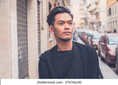 Young handsome Asian model dressed in black tunic posing in the city streets
