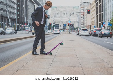 Young handsome Asian model dressed in dark suit and tie posing with his skateboard
