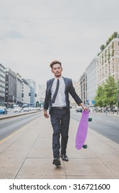 Young handsome Asian model dressed in dark suit and tie walking with his skateboard