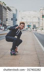 Young handsome Asian model dressed in dark suit and tie riding his skateboard while talking on phone