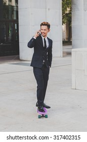 Young handsome Asian model dressed in dark suit and tie talking on phone while skateboarding