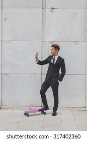 Young handsome Asian model dressed in dark suit and tie taking a selfie