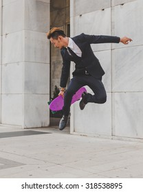 Young handsome Asian model dressed in dark suit and tie jumping with his skateboard