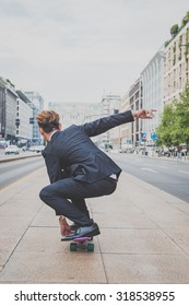 Young handsome Asian model dressed in dark suit and tie riding his skateboard