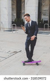 Young handsome Asian model dressed in dark suit and tie texting in the city streets