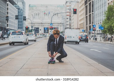 Young handsome Asian model dressed in dark suit and tie posing on his skateboard